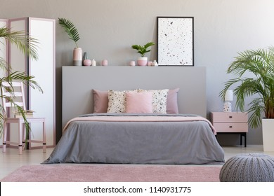 Poster on grey bedhead in bedroom interior with pink pillows on bed next to chair. Real photo
