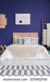 Poster on purple wall above bed with wooden bedhead and knit blanket in cozy bedroom interior