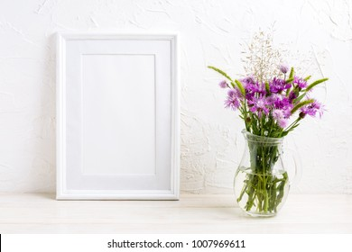 Poster white frame mockup with purple burdock flowers in the glass vase. Empty frame mock up for artwork presentation