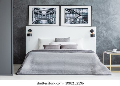 Posters above bed with grey blanket in simple hotel room interior with concrete wall