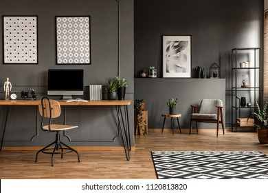 Posters on grey wall above wooden desk with computer monitor in open space interior