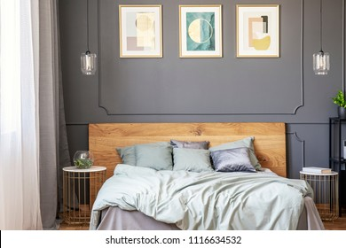 Posters on grey wall with molding above bed with wooden bedhead in bedroom interior. Real photo