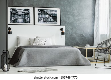Posters on white bedhead of bed with grey bedding near lantern in bedroom interior with concrete wall