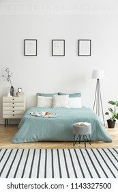 Posters on white wall above green bed in bedroom interior with striped carpet. Real photo
