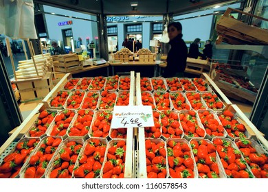 Postgalerie Karlsruhe, Germany, May 15, 2010 - Woman sells strawberries on a stalk at Postgalerie Karlsruhe shopping mall