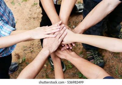 Posting back hand to the center of group of people in circle to represent victory, fight, unity, collaborative, teamwork.