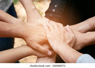 Posting back hand to the center of group of people to represent victory, fight, unity, collaborative, teamwork.