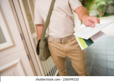 Postman delivering a letter outside a home