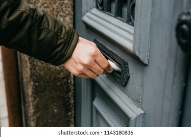 The postman puts a letter or newspaper or magazine in the mailbox at the door of a residential building or a person puts a brochure with advertising. Close-up.