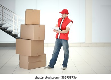 Postman in red jacket near pile of carton boxes in the room