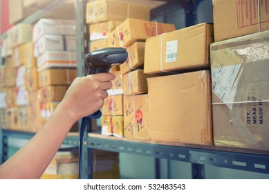 Postman worker scanning package with barcode scanner in warehouse for delivery.