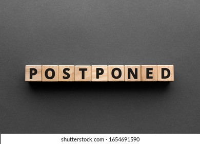 Postponed - words from wooden blocks with letters, postponed concept, top view gray background