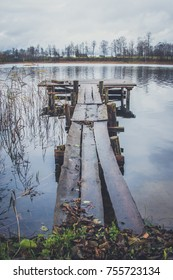Posts of a broken pier leading out into calm blue tranquil water