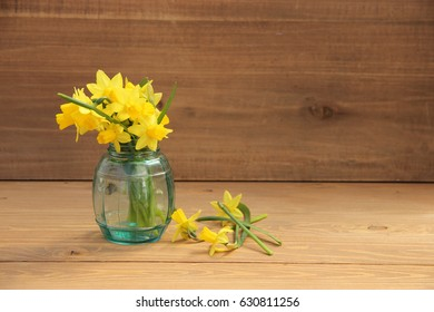 Posy of bright yellow daffodils on wooden table with copy space