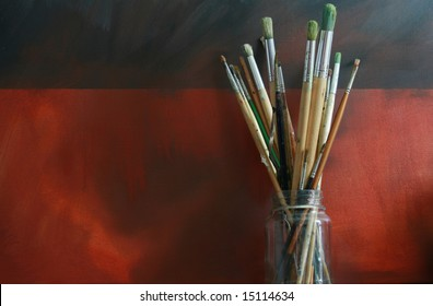 A pot of artists paint brushes in a glass jar set against an oil painted 'Grunge' styled canvas background. Copy space available.