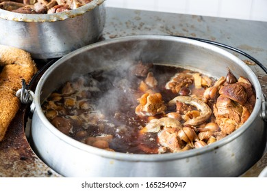 Pot of bak kut teh being cooked in restaurant consisting pork and herbal soup