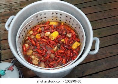 Pot And Basket Of Hot Boiled Louisiana Crawfish With Potatoes,Corn, Garlic, Mushrooms  And Sausage