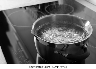 Pot with boiling water on electric stove, space for text