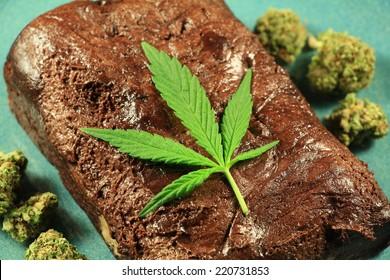Pot Brownie 6. A marijuana leaf on a marijuana brownie on a blue plate with buds.