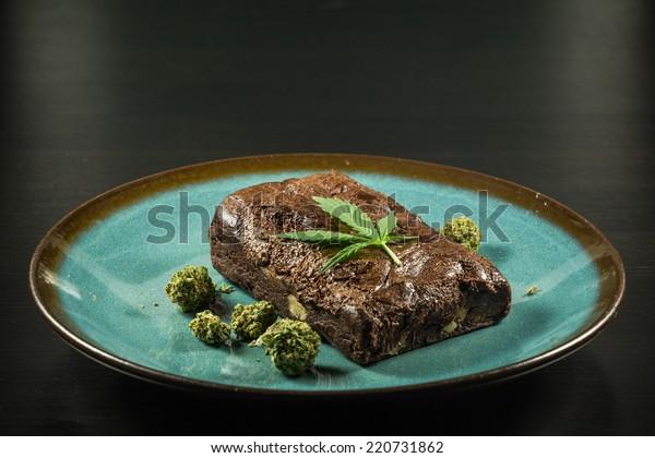 Pot Brownie 8. A marijuana leaf on a marijuana brownie on a blue plate with buds.