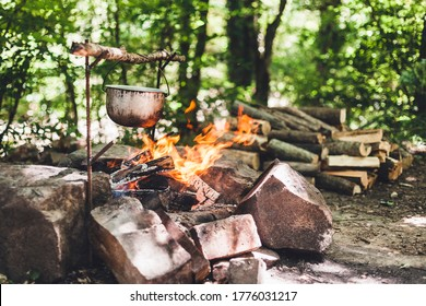 The pot is burning near the tent in the forest at night. Beautiful campfire in a tourist camp in the wild. Survival in the forest. Cauldron over the fire. Oven for cooking on a fire.