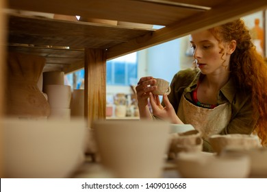 Pot collection. Good-looking long-haired ginger woman checking tiny clay cup while checking finished figures