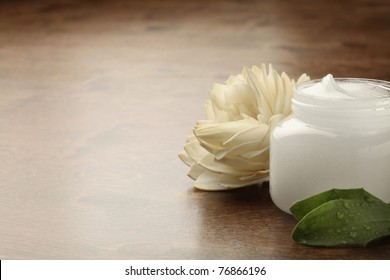 pot of cosmetic creme on a wooden surface