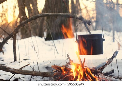 A pot in the fire, water is heated in the winter forest a
