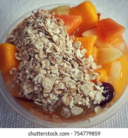 pot of fruit salad with papaya grape and apple mango with a layer of oats over a white cloth