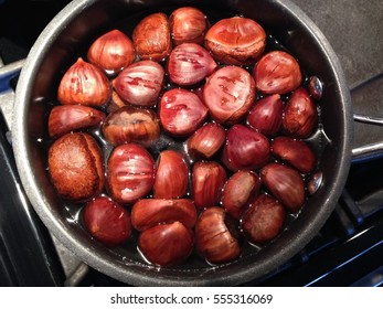 A pot full of chestnuts being boiled over a gas flame, seen from above
