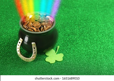 Pot with gold coins, horseshoe and clover on green background, space for text. St. Patrick's Day celebration