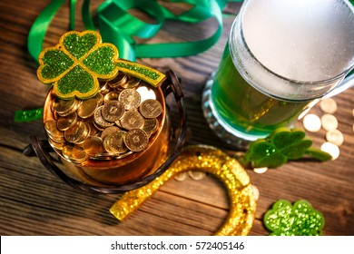 Pot of gold, green beer and shamrocks on wooden background