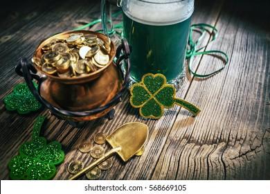 Pot d'or avec pelle, bière et shamcailloux sur fond bois