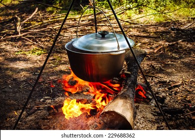 pot hanging over the fire in the forest in a hike, the water vapor from the boiler