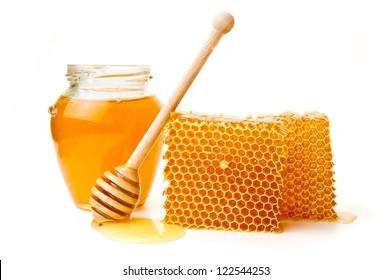 Pot of honey and wooden stick are on a table