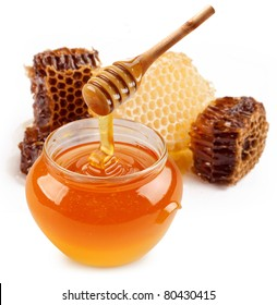 Pot of honey and wooden honey stick are on a table.