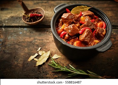 Pot of hungarian goulash on rustic wood background with chili peppers and laurel and copy space