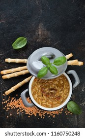 Pot of italian thick soup with pasta and lentils on a dark brown stone background, top view with copyspace, vertical shot