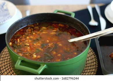 Pot of minestrone soup on a table. Selective focus.