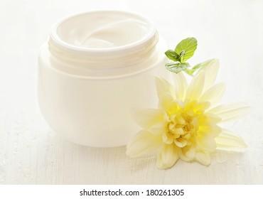 pot of moisturizing face cream and beautiful flowers