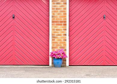 Pot of pink flowers in front of red garage doors