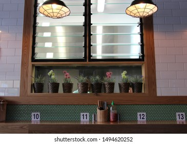 Pot plants and table numbers in a restaurant / cafe setting