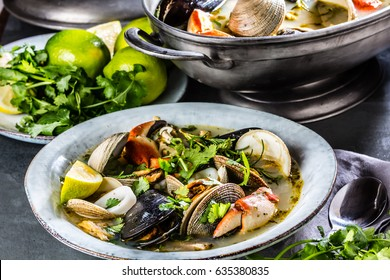 Pot and plate of Seafood shellfish soup of mussels, crabs, clams and other shellfish. Slate background
