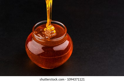 Pot of pouring honey on black background with copy space