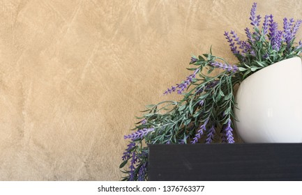 pot with purple little flowers over brown wall, copy-space left