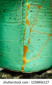 A pot repaired with the Japanese art form of kintsugi using urushi lacquer and gold powder.  Shot with a shallow DOF.