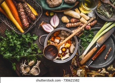 Pot with sliced colorful vegetables and cooking spoon on dark rustic table background with organic vegetarian ingredients and kitchen tools , top view. Healthy and clean food and eating  concept.