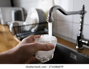 potable water and safe to drink. man filling a glass of water from a stainless steel kitchen tap. male's hand pouring water into the glass from chrome faucet to drink running water with air bubbles.