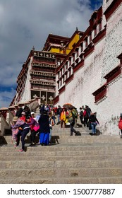 POTALA PALACE, LHASA, TIBET, CHINA; OCTOBER 2018: VERICAL: Tourists walk up and down a stairwell leading up to the beautiful Potala Palace. Travelers visit the ancient Dalai Lama's winter residence.