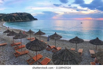 Potami beach scenic view to Ionian Sea, sun beds and umbrellas during sunset, Himara town, Albania